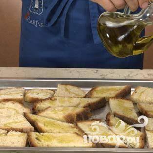 Выложить ломтики хлеба на противень, щедро полить оливковым маслом и запечь в духовке около 3-5 минут.