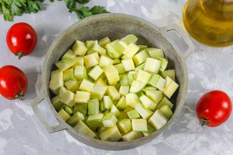 Кабачки промойте в воде, срежьте хвостики с обеих сторон каждого овоща. Нарежьте плоды пластинами, а пластины - кубиками и высыпьте нарезку в казан.