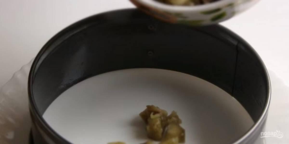 4. Нарежьте остывшие баклажаны кубиками, добавьте измельченный чеснок, щепотку соли и перемешайте. Соберите салат: разъемную форму смажьте растительным маслом и поставьте на блюдо нижней частью вверх.