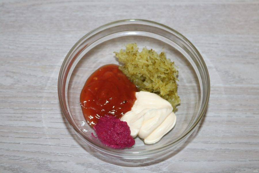 Приготовьте соус.  Огурец натрите на мелкой тёрке. В глубокой тарелке соедените майонез, кетчуп, хрен и огурец.