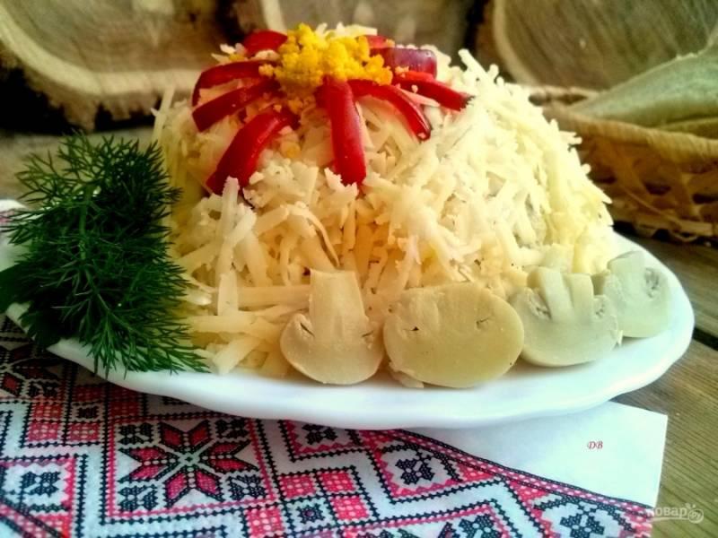 Выложите салат на плоское блюдо в виде купола, присыпьте тертым сыром. Красный перец нарежьте тонкими полосками, выложите из них цветок, серединку присыпьте тертым желтком. Приятного аппетита!