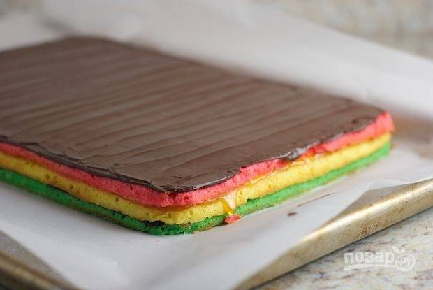 Когда коржи пропитаются, растопите черный шоколад и покройте печенье равномерным слоем.