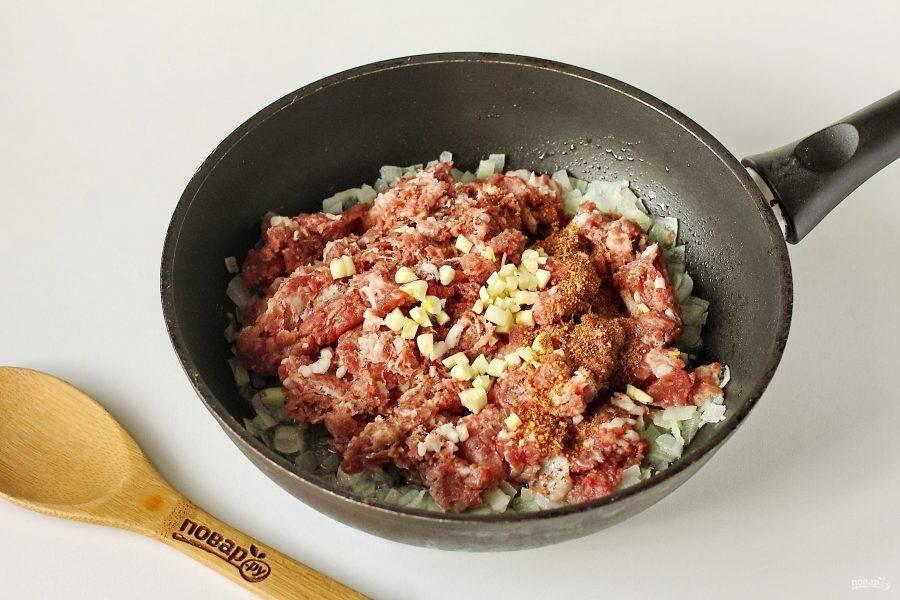 Обжарьте лук на растительном масле до мягкости, добавьте фарш, соль и специи по вкусу. Обжарьте все вместе в течение 3-5 минут, разбивая комочки фарша лопаткой.