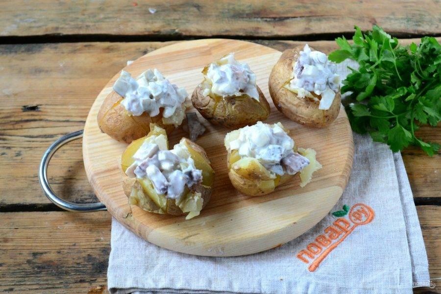 На каждой картофелине сделайте неглубокий крестообразный разрез и разверните края. В получившиеся небольшие кармашки положите по 1 ст. ложке селедочного соуса.