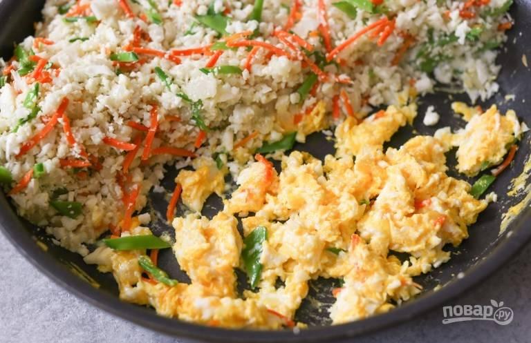 В отдельной емкости взбейте яйца. Капусту с овощами сдвиньте с одной половины сковороды, обжарьте яйцо.