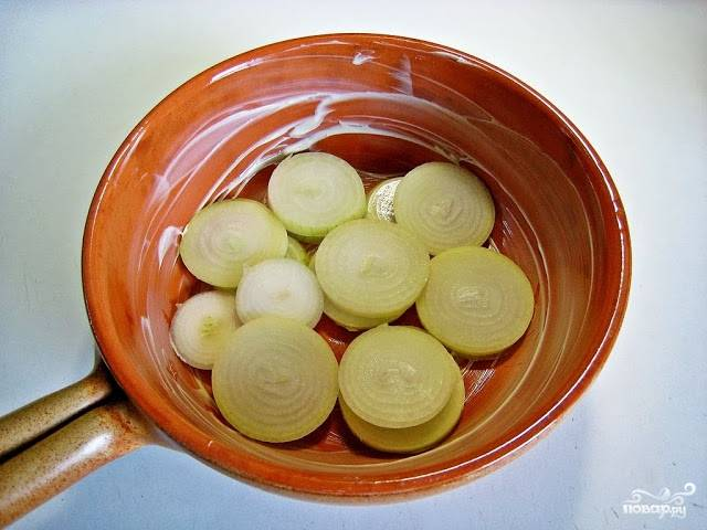 1. Дно формы для запекания смажем маслом, на дно выкладываем лук колечками.