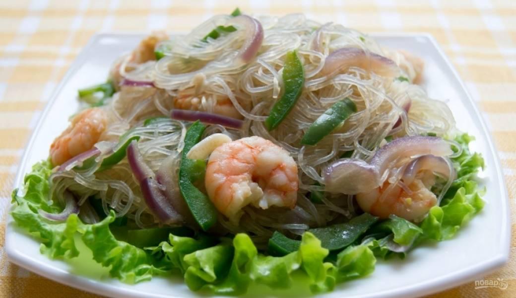 Выложите на блюдо листья салата, а на них — вермишель с креветками и овощами. Соус, который остался в сковородке, подайте отдельно (или полейте им блюдо).