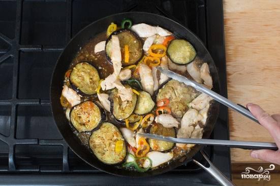 4. Когда курочка хорошо проготовится, а овощи станут мягким, выложите на сковороду баклажаны. Жарьте еще несколько минут. Добавьте томатный соус, аккуратно перемешайте.