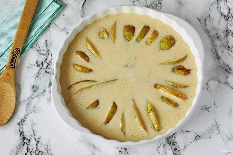 Форму для выпечки (у меня примерно 27 см. в диаметре) смажьте маслом и присыпьте мукой или манкой. Вылейте тесто, а сверху разложите груши. Выпекайте в духовке при температуре 200 градусов около 30 минут.