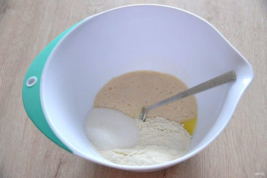 Добавьте муку, сахар, соль, влейте опару, замесите тесто.