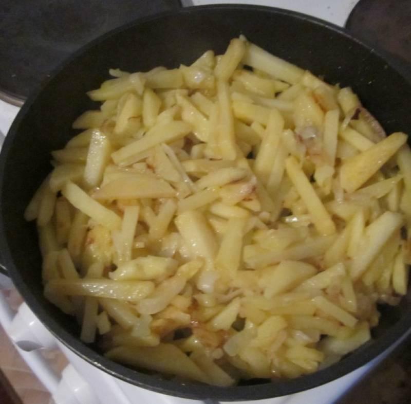 Разогрейте сковородку, влейте побольше масла. Жарим картошку до готовности вместе с луком.