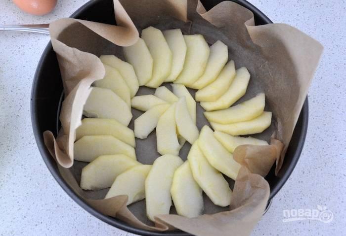 3.Очистите яблоки от кожуры и нарежьте их тонкими дольками, форму для выпечки застелите пергаментом и выложите яблоки веером.