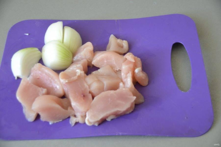Для фарша порежьте кусочки курицы и лук.