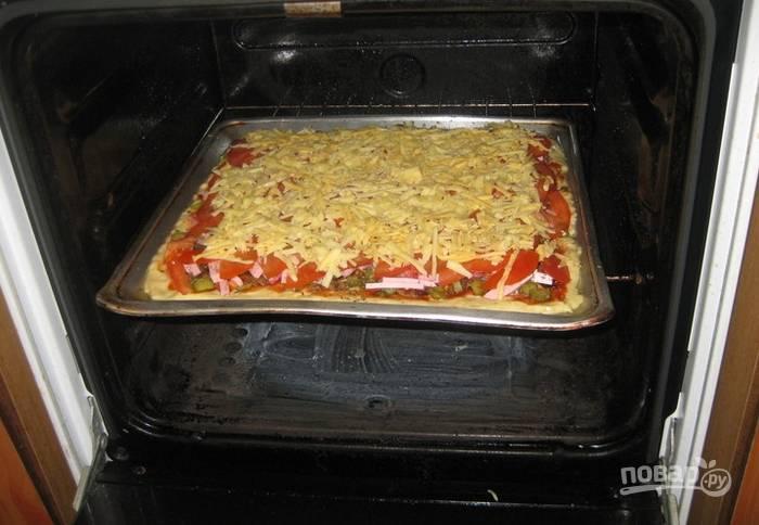 Посыпаем верхушку пиццы тертым сыром. Отправляем в духовку запекаться. Температура — 180 градусов. Время запекания зависит от вашей духовки, обычно это занимает не более 30 минут.