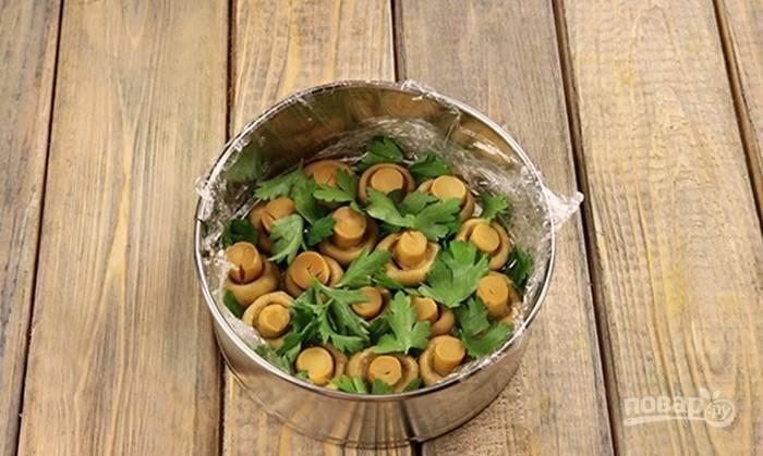 Прежде отварите яйца вкрутую, а морковь и картофель — до готовности. Глубокую круглую форму застелите пищевой плёнкой. На дно уложите шампиньоны вниз шляпками и листочки петрушки.