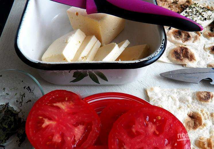 Сыр нарезаем ломтиками. Томат моем под водой и нарезаем кружочками.