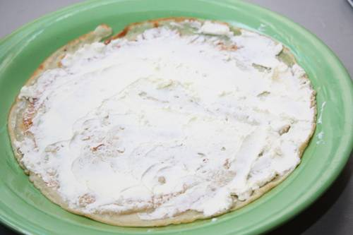 2. Первый блин смазываем творожным сыром. При желании в сам сыр можно добавить специи или зелень.