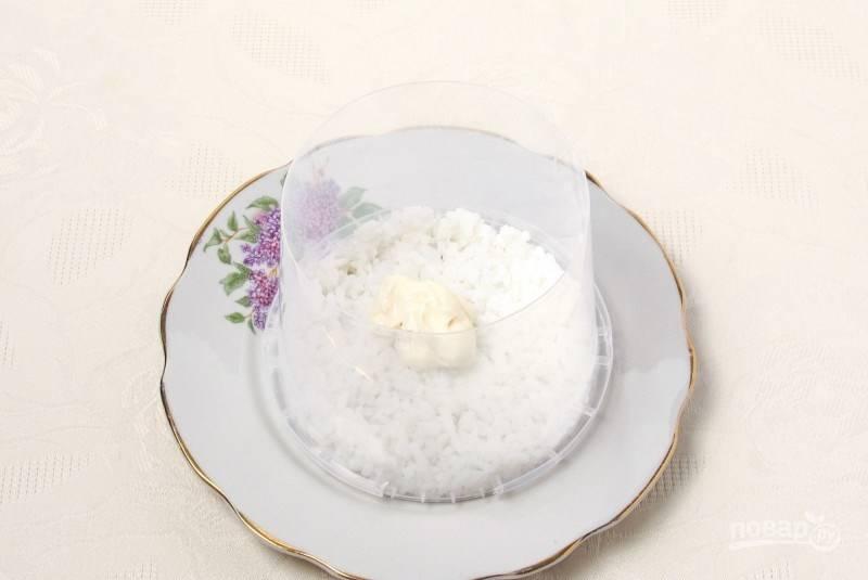 В кастрюле вскипятите воду, бросьте в нее рис, посолите и отварите до готовности. Возьмите кулинарное кольцо, поставьте его в центр тарелки для подачи. Положите в нее слой риса, слегка утрамбуйте. Положите на рис столовую ложку майонеза и разровняйте.