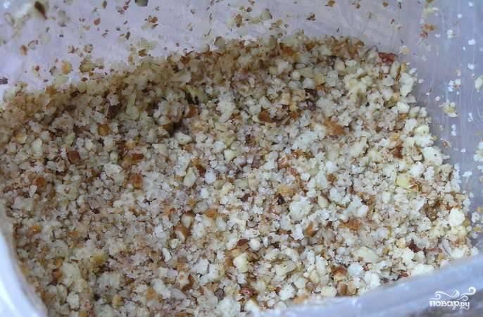 В продолговатую форму положите пегамент для запекания и смажьте его сливочным маслом. Орехи с печеньем выложите в форму, хорошенько их утрамбовав.
