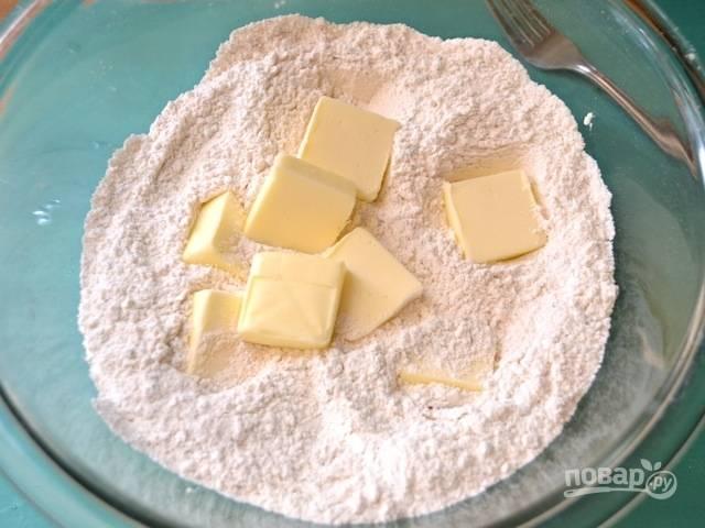2.Нарежьте холодное сливочное масло и выложите его в мучную смесь.