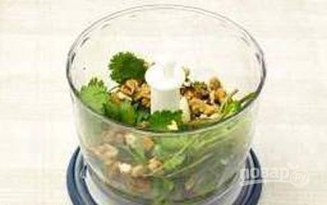 В чашу блендера отправьте чеснок, кинзу и орехи. Измельчите все до однородности.