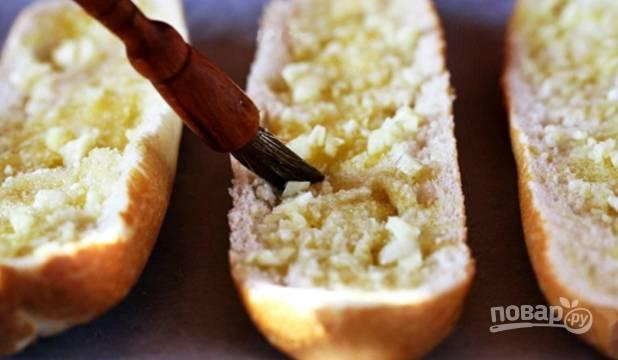Затем хлеб смажьте чесночным маслом. Сверху натрите сыр.