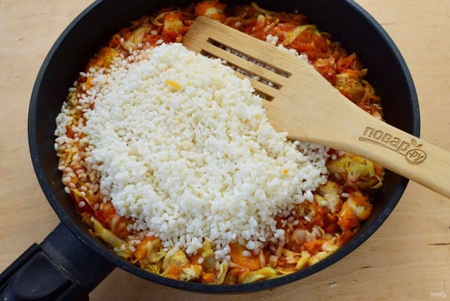 Добавьте промытый рис, залейте водой или бульоном (2 стак.). Доведите до кипения, накройте крышкой и тушите на медленном огне в течение 30 минут до готовности риса. Крышку не поднимайте, дайте рису хорошенько пропариться и стать рассыпчатым.