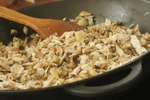 Добавляем к луку куриное филе и грибочки. Обжариваем несколько минут, помешивая. Затем добавляем сметану и измельченный укроп. Также кладем орегано и соль по вкусу. Готовим еще 5-7 минут.