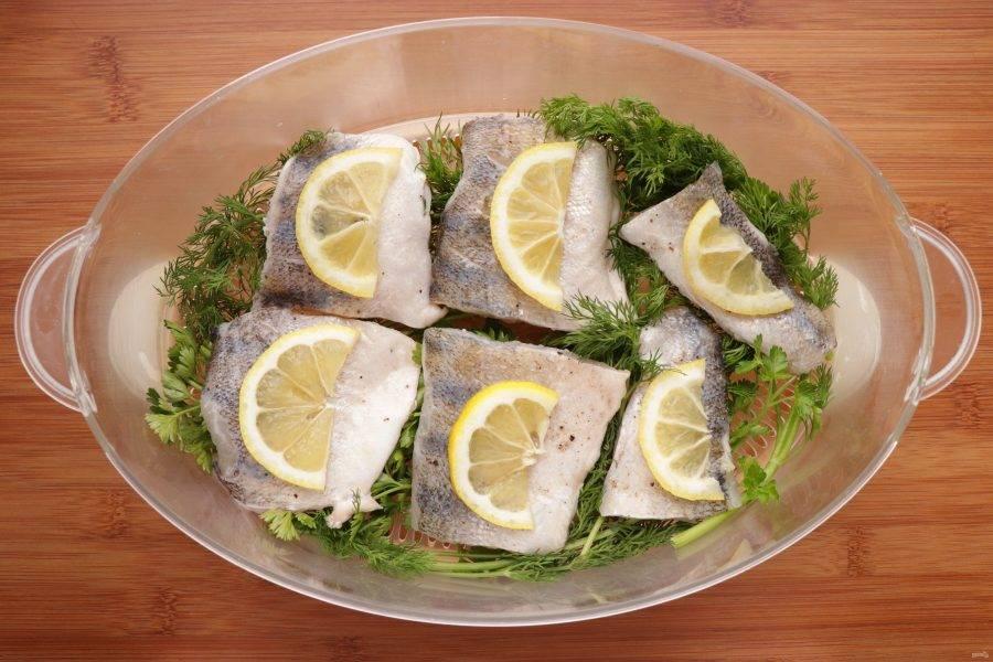 Лимон нарежьте полукольцами и на каждый кусочек рыбы положите по одной дольке.
