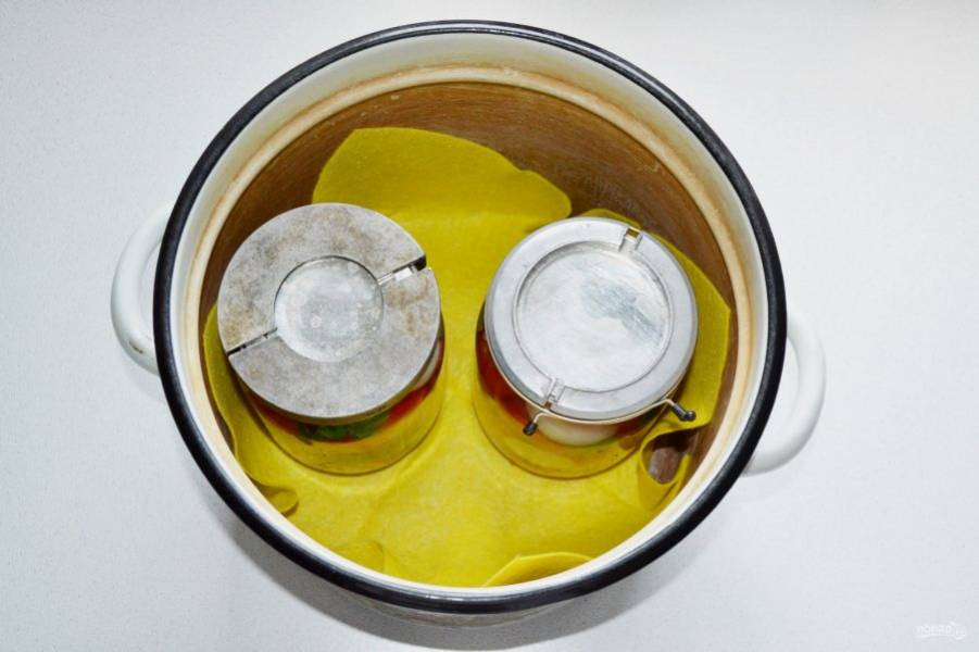 """И отправьте заготовку стерилизоваться. Для этого поставьте банки в большую кастрюлю, застелив дно тканью. Влейте воду, чтобы она доходила до """"плечиков"""" банки. После закипания воды стерилизуйте 15 минут."""