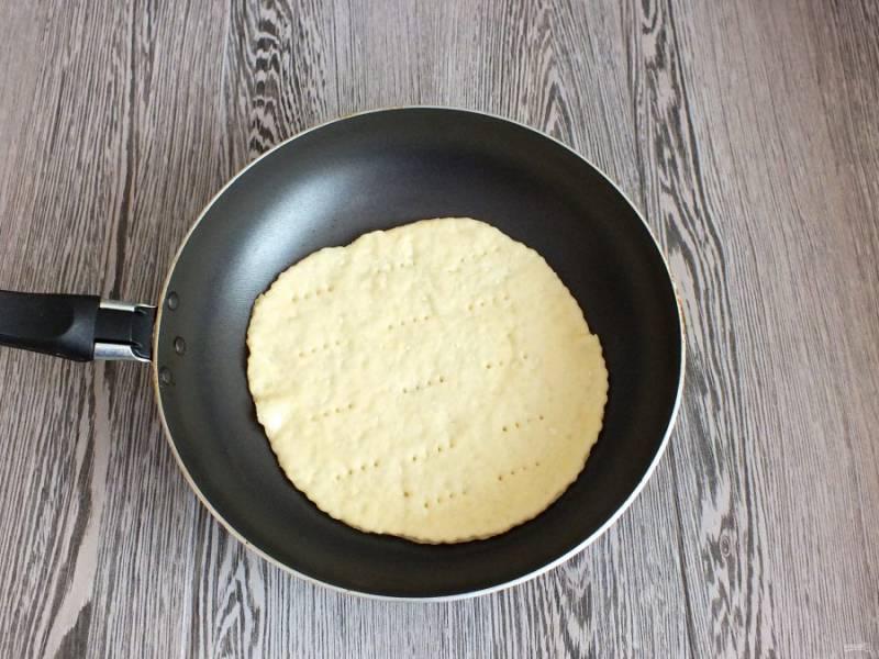 Разогрейте сковороду и убавьте огонь до чуть ниже среднего. Корж наколите вилкой и переложите на сковороду. Обжаривайте с одной стороны 2-3 минуты. Постарайтесь отрегулировать огонь, чтобы корж не горел, а равномерно пропекался.
