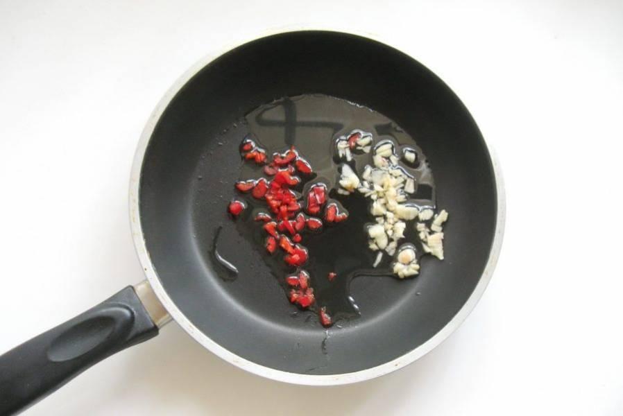 Красный жгучий перец, чеснок помойте и мелко нарежьте. Выложите в сковороду с подсолнечным маслом.