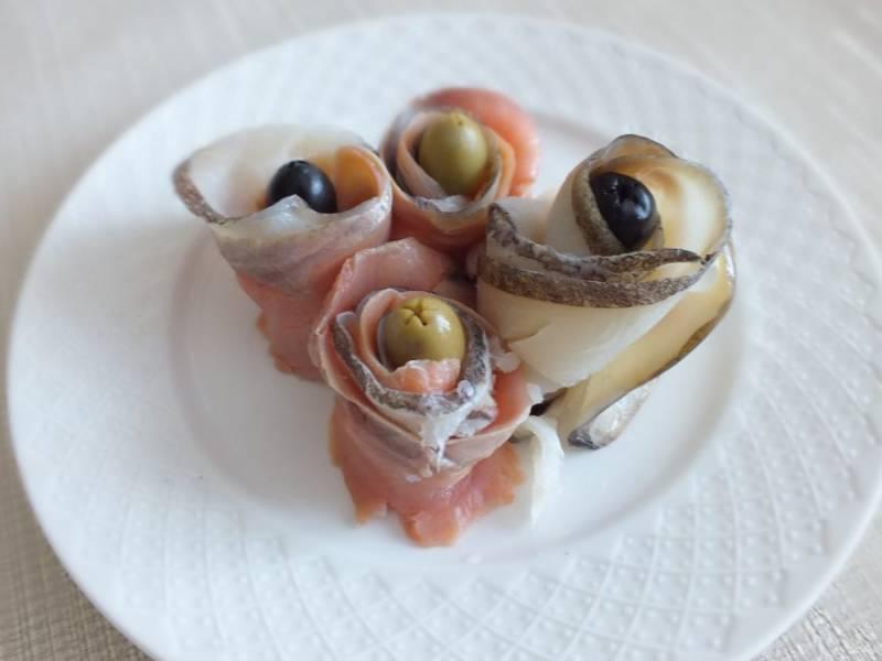 """Повторите процесс с остальными кусочками рыбы и установите на блюдо. В центр """"розочки"""" положите оливки и маслины."""
