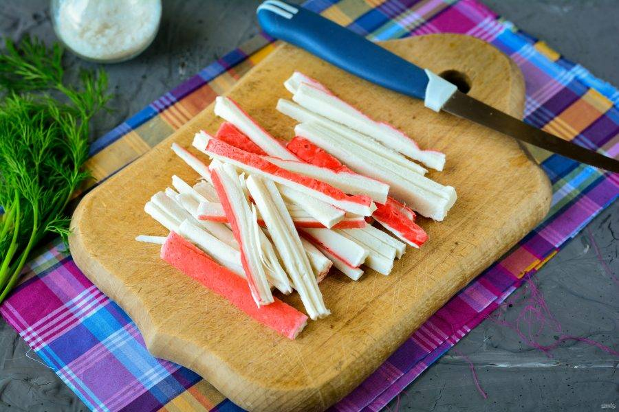 Размороженные крабовые палочки нарежьте полосками.