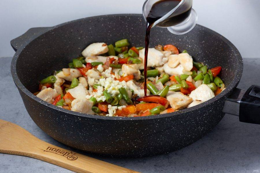 В последнюю очередь в сковороду добавьте рубленный чеснок, готовое куриное филе и соевый соус.