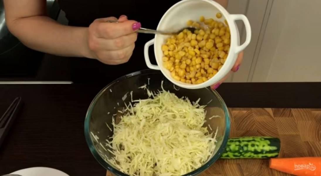 1. Капусту нашинкуйте тонкой соломкой, переложите в миску, посолите и слегка разомните руками, чтобы она пустила сок и стала более мягкой. Добавьте консервированную кукурузу.