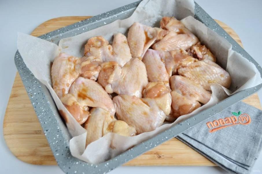 4. Застелите противень пергаментом, смажьте маслом растительным. Положите крылышки в один слой, полейте маринадом, отправьте в заранее разогретую до 200 градусов духовку на 40 минут.