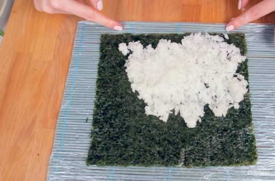 1. Для начала отварите и заправьте рис так, как это необходимо сделать для приготовления суши или онигири. Далее положите лист нори на застеленный пищевой пленкой коврик для суши и слегка сбрызните его рисовым уксусом.