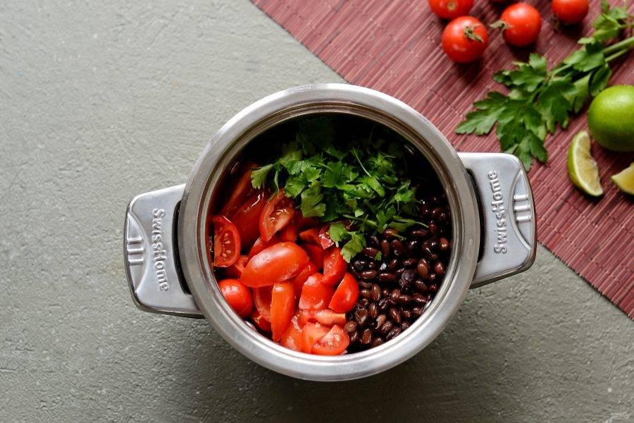 Петрушку крупно порубите, томаты разрежьте на четвертинки, болгарский перец нарежьте кубиками. Добавьте овощи, чёрную фасоль и половину петрушки в кастрюлю. Потушите 2-3 минуты.