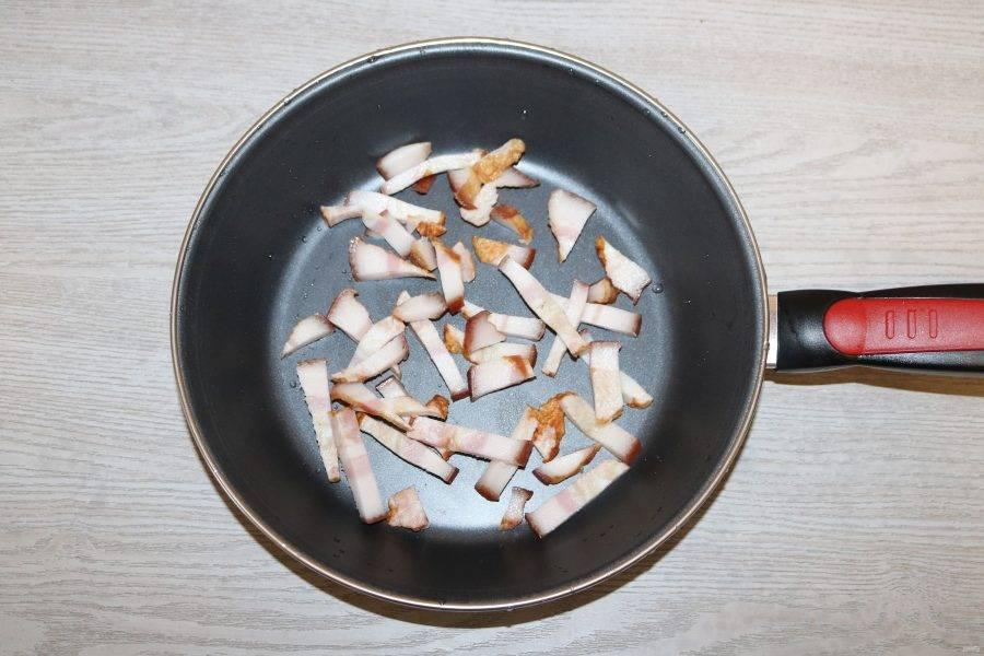 В сковороде на среднем огне обжарьте бекон.