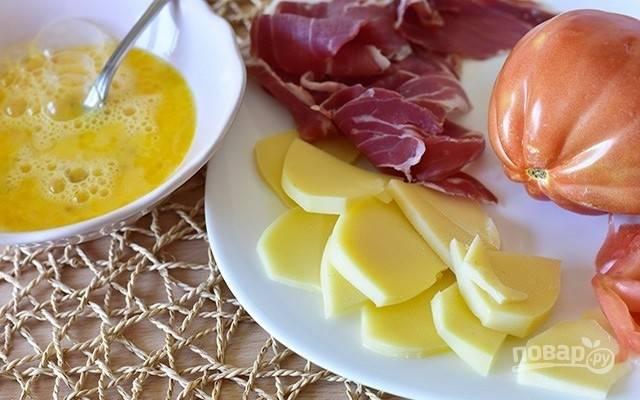 2.Яйца взбейте в миске. Сыр и ветчину нарежьте ломтиками.