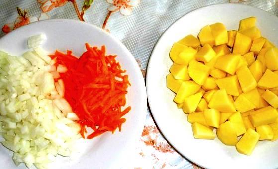 Теперь принимаемся за овощи. Картошку чистим, режем кубиками, лук мелко рубим, морковь трем на терке. Часть лука положим в фарш, часть — просто в суп.