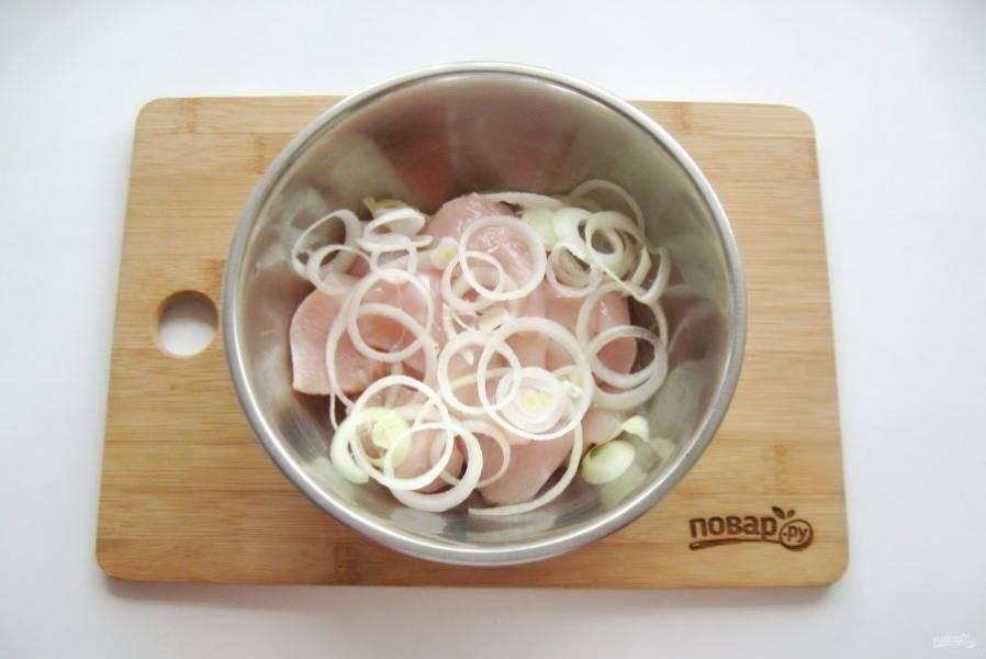 Репчатый лук очистите, помойте и нарежьте кольцами. Добавьте в миску с куриным филе.