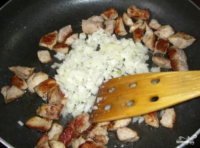 2. Почистите лук. Нарежьте его средними кубиками. Отправьте к жарящемуся мясу, когда у него появится золотистая корочка.