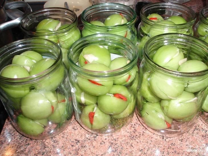 1. Промойте помидоры, сделайте неглубокий надрез с одной стороны. Почистите и нарежьте пластинками чеснок, горький перец нарежьте небольшими кусочками. Пару пластинок чеснока и кусочек перца вложите в надрез помидора.