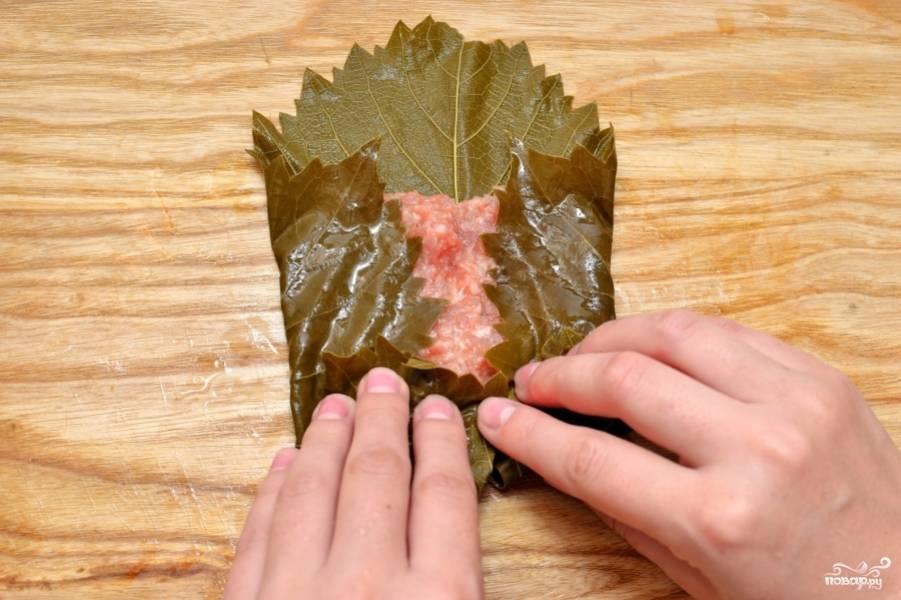 Возьмите один виноградный лист. Разложите его на столе. В середину листа положите столовую ложку начинки из фарша. И аккуратно заверните.