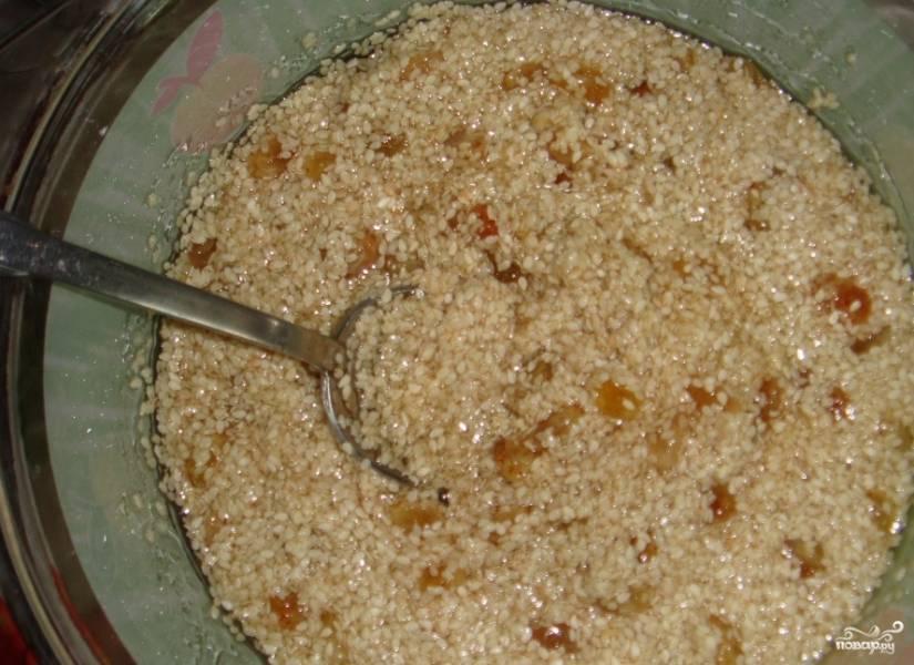 Положите сырой кунжут в сито и хорошенько промойте под струей прохладной воды. Переложите кунжут в миску. Вымойте изюм и отправьте к кунжуту. Лучше брать изюм светлых сортов. Добавьте к ингредиентам жидкий мед.