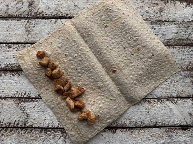 Возьмите лист лаваша, разрежьте его на несколько частей. На лаваш выложите жареное куриное филе.