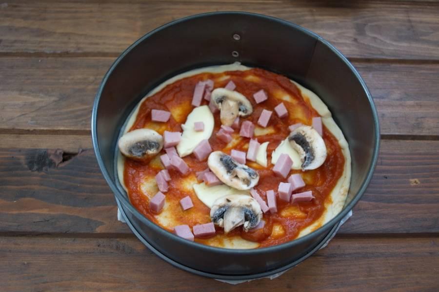 Нарезать колбасу. Нарезать грибы. Выложить начинку так, чтоб она лежала равномерно по всей поверхности.