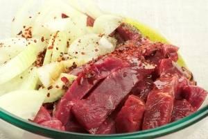 В глубокой емкости соединяем мясо, лук, оливковое масло, соевый соус и специи.